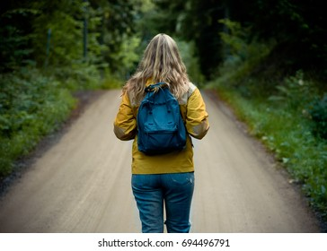 Girl with backpack hikes through the forest in Sweden
