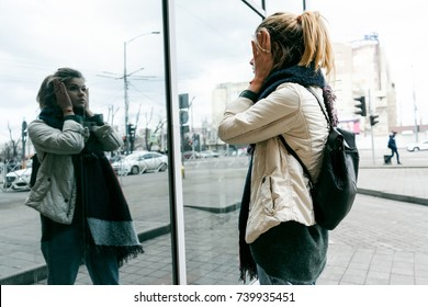 girl with a backpack on a city street looks at her reflection in the mirror
