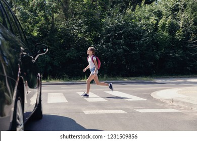 Girl with backpack running through a pedestrian crossing next to car