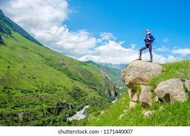 A girl with a backpack is standing on a rock. Mountain landscape. Mountain climbing in the Caucasus.