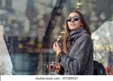 Girl with a backpack is traveling around the city, enjoying the music from her smartphone. She is dressed in a gray coat, she has a scarf around her neck, earphones in her ears.