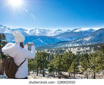 Girl with backpack using her phone on a winter hiking trip in Colorado .Rocky Mountain National Park. Close to Estes Park, Colorado, USA