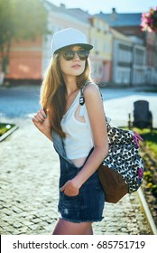 Girl with backpack walking around city in good day. Outdoor portrait of smiling female traveler in hat posing with beautiful architecture on background