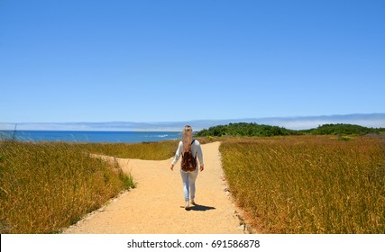 Girl with backpack walking on the road , at forked road making decision which way to go. Hiking trip by the Pacific ocean. Año Nuevo State Park is a state park of California, USA