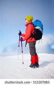 girl with backpack walking on snow in the mountains and mountain climbing during the winter holidays.