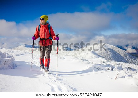 girl with backpack walking on snow in the mountains and mountain climbing  during the winter holidays f928ba981