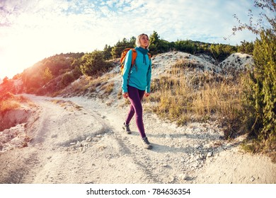 A girl with a backpack walks along the mountain path against a beautiful blue sky with clouds. A woman walks along a stony path. A blonde is traveling with a backpack.