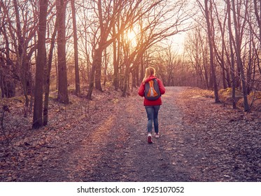 A girl with a backpack walks in a leafy autumn park in the rays of the setting sun