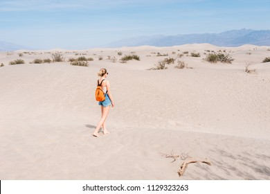 Girl with backpack walks on the desert in the lowest point on earth in Death valley, USA, West Coast