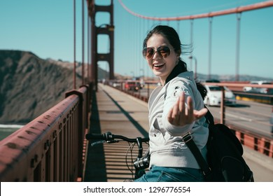 girl backpacker riding bike on pedestrian on golden gate bridge. young asian charming lady moving finger cheerful smiling telling invite people to come with her recording travel tour in san francisco.