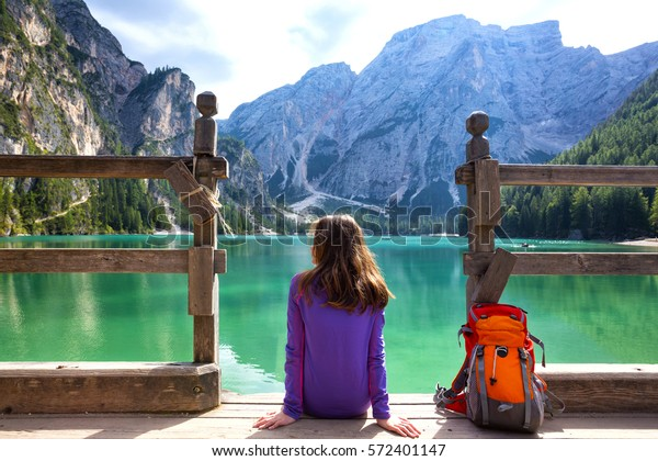 girl backpacker sitting on a pier and looking at Braies lake, Dolomites Italy