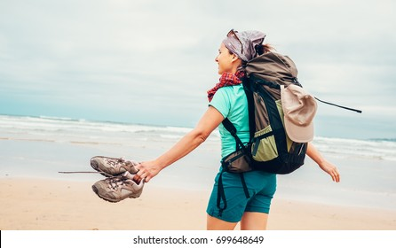 Girl backpacker traveler enjoys with fresh ocean wind