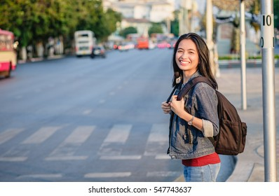 girl with bag smiling on street in Bangkok, across the road