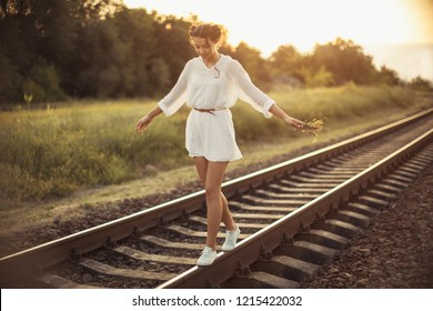 Girl balancing on train rail. Attractive young woman walking outdoors