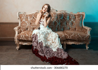 Girl in a ball gown sitting on the couch and cuddle kittens.
