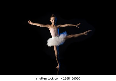 Girl ballerina gymnast in white dress posing on a black background in the studio