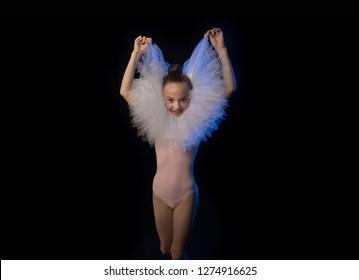 Girl ballerina gymnast in white dress posing on a black background in the studio