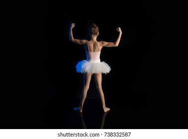 Girl ballerina posing and performing dance elements and pose in blue scenic light on a black background