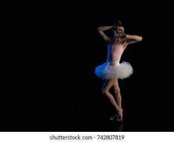 Girl ballerina posing and performing dance elements in blue scenic light on a black background