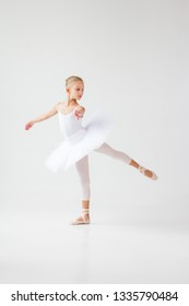 A girl ballerina in a white trick and white tutu on a light background performs exercises