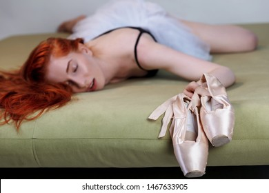 Girl ballet dancer tired and asleep. Redhead ballerina funny sleeps in bed after a hard training and holds his pointe shoes firmly in his hands