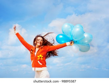 Girl with balloons under blue sky with clouds