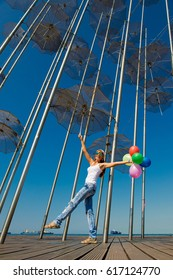 Girl with balloons under the umbrella. Concept of summer travel. Umbrellas in Thessaloniki, Greece. Installation Flying umbrellas, Greece. Group of umbrellas on blue sky background