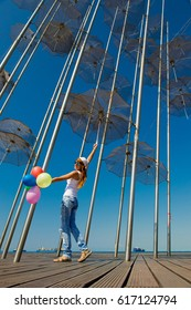 Girl with balloons under the umbrella. Concept of summer travel. Umbrellas in Thessaloniki, Greece. Installation Flying umbrellas, Greece. Group of umbrellas on blue sky background