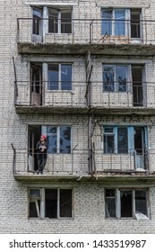Girl in a bandana on the balcony of an abandoned and cracked empty high-rise building. Post apocalypse