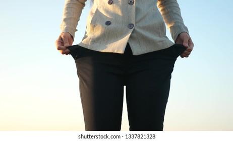 Girl is bankrupt. Beggar business. Ruined enterprise. Woman debtor turns out empty pockets against blue sky.