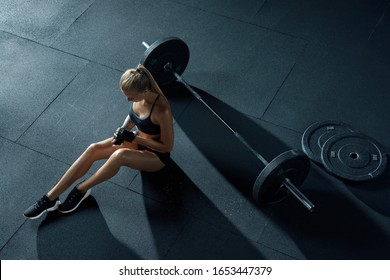 Girl with a barbell. Crossfit woman sits on the floor in the gym takes off gloves, resting after cross-fit training with barbell. Top view. Concept of strength, healthy lifestyle, sport.