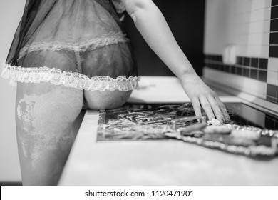 a girl with bare buttocks sits on a table stained with flour in a black and white photo