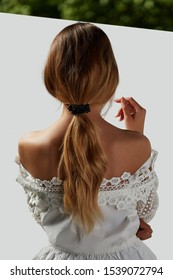 A girl with bare shoulders in a white top is standing with her back. Long hair is collected by a ribbon with pearls. The photo is taking on a white background with a green stripe at the top.