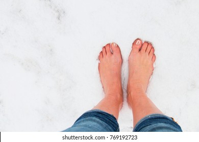 girl barefoot stands in cold snow, in winter