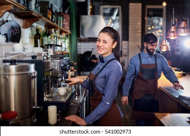 Girl barista bartender waiter in uniform making coffee at the bar