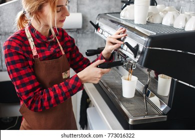 Girl Barista in the red shirt makes the coffee. Close-up of hands