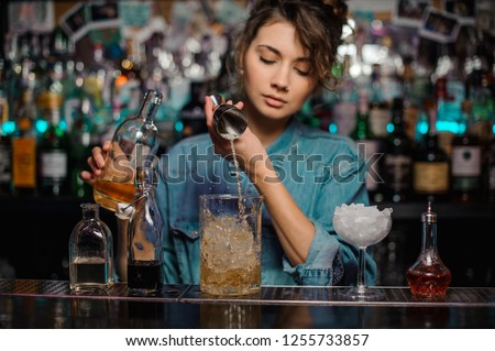 Girl bartender pouring to the measuring glass cup with ice cubes an alcoholic drink from jigger on the bar counter on the blurred background