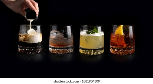 Girl bartender pours cream and prepares a set of classic cold alcoholic cocktails in transparent glasses on a black background. White Russian, Bramble, Whiskey Sour and Negroni.