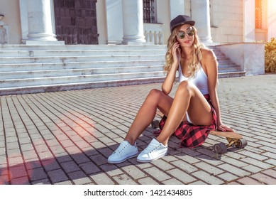 A girl baseball cap makes telephone call, summer skateboard sits in city, online internet application listens voice message, social networks. Fashion lifestyle, modern idea concept trends. Free space