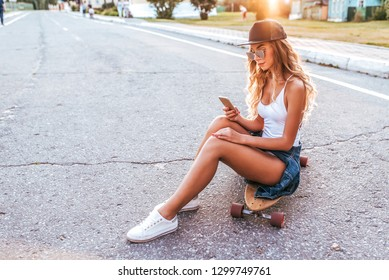 A girl in baseball cap sits on skateboard, longboard. In summer in city on background of an asphalt road, a young woman. In his hand a smartphone, an application to the Internet. Free space for text.