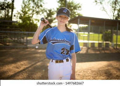 Girl baseball players with bat on the playground