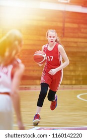 Girl basketball player with a ball in the game