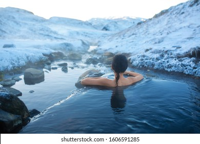 The girl bathes in a hot spring in the open air with a gorgeous view of the snowy mountains. Incredible iceland in winter.