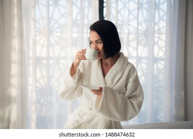 A girl in a bathrobe drinking coffee in the morning on the bed in a light room.