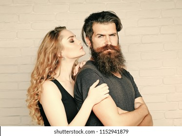 Girl and bearded hipster. Man with beard and woman with long blond hair. Hipsterism, subculture, trend. Couple in love hug on white brick wall. Fashion, beauty, style concept.