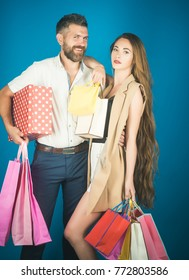Girl and bearded man hold present pack, cyber Monday. Shopping and sale. Black Friday, happy holiday, relations. Fashion shopaholic couple. Couple in love hold shopping bag near blue wall.