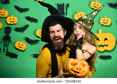 Girl and bearded man with smiling faces on green background with decor. Wizard and little witch in black hats hug holding pumpkin. Halloween party and celebration concept. Dad and daughter in costumes