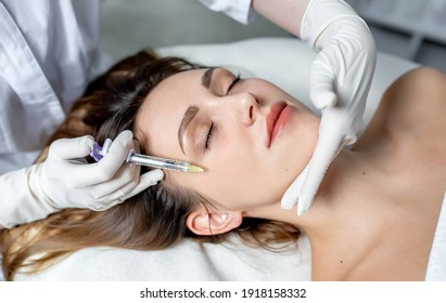 Girl beautician makes injections on the lips and face of a beautiful woman in a cosmetic wedge. Cosmetology concept.