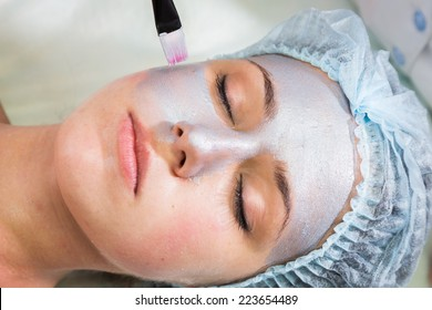 Girl with a beautician at spa salon. Beautician performs cosmetic procedures.applying cosmetic mask by brush. Cosmetology, facial, beauty - The concept of facial skin care. Article about cosmetology.