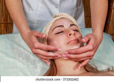 Girl with a beautician at spa salon. Beautician performs cosmetic procedures.applying cosmetic cream. Cosmetology, facial, beauty - The concept of facial skin care. Article about cosmetology.